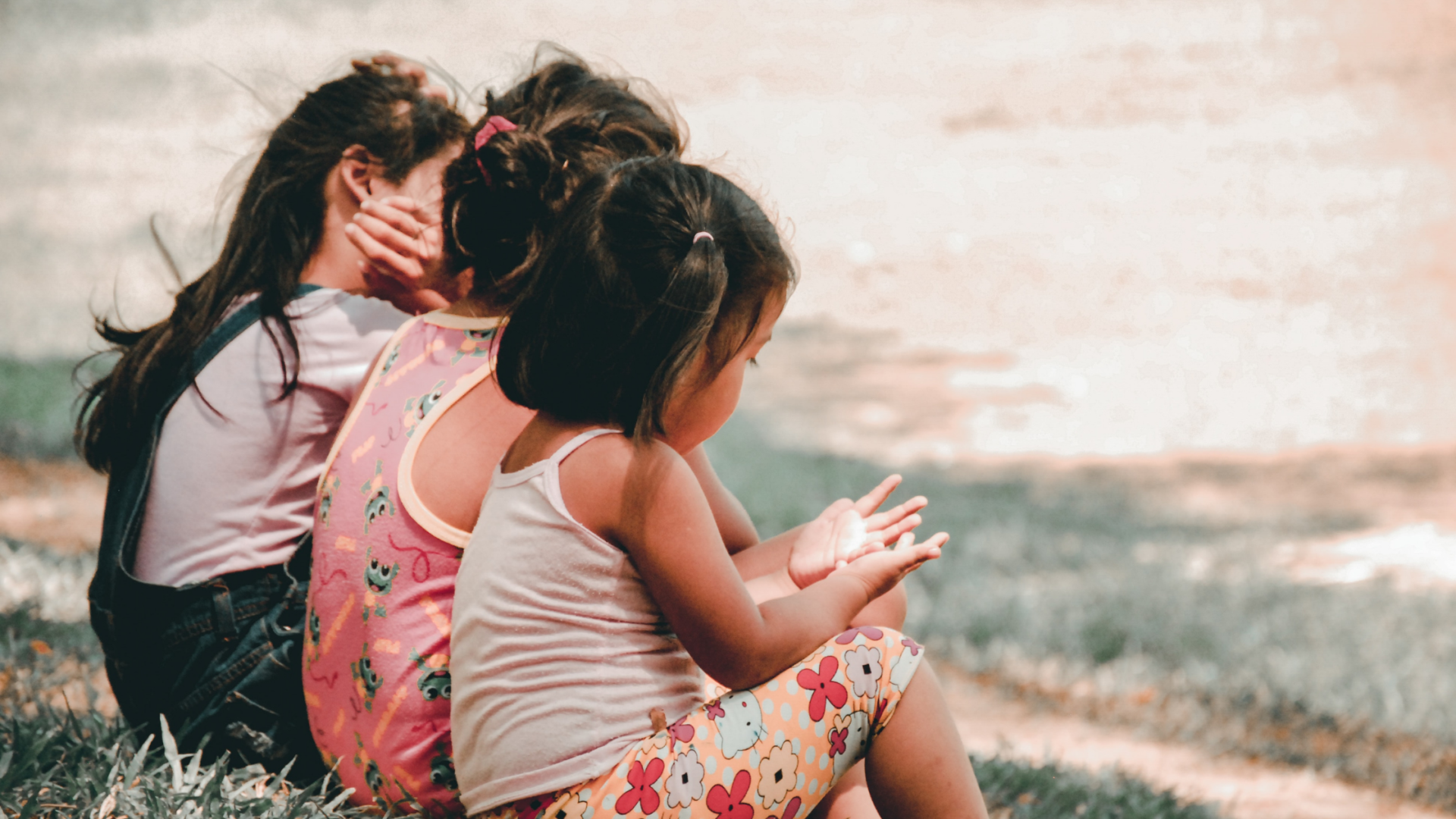 three little girls photographed sitting down from behind