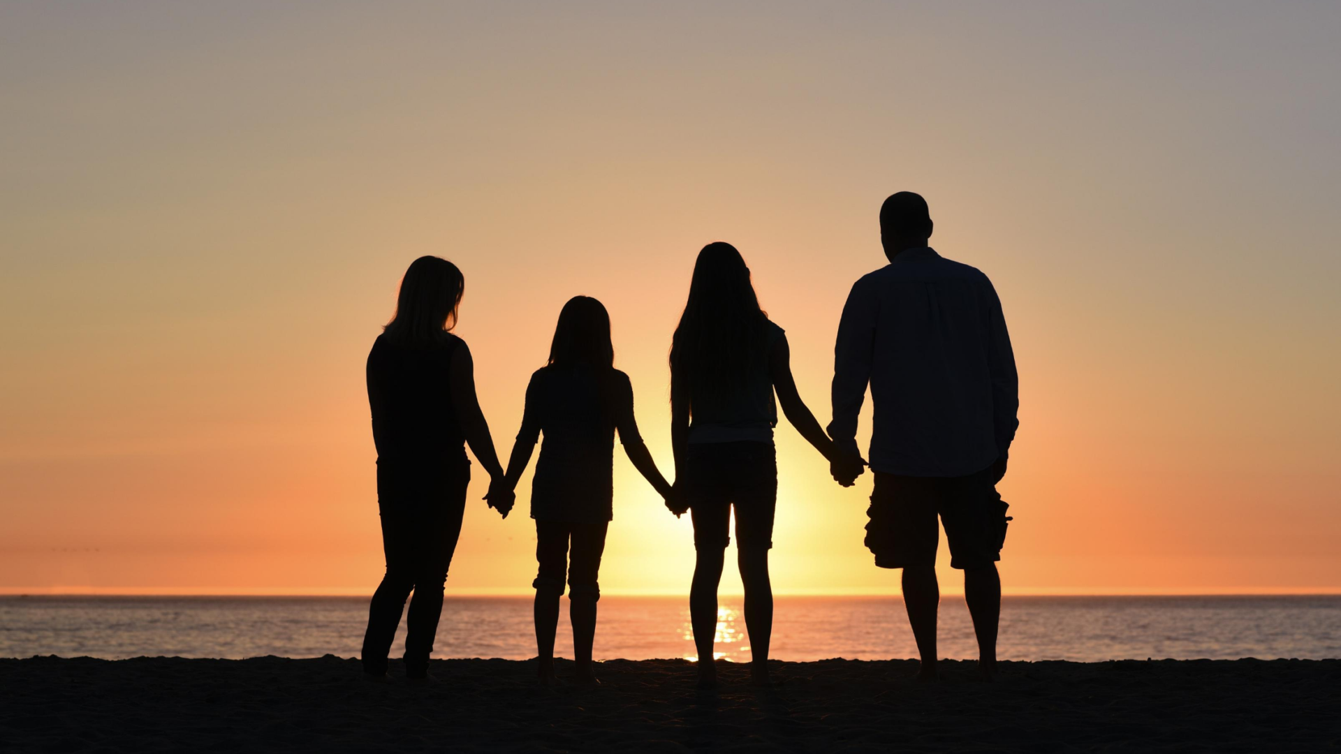mother, two daughter, and dad holding hands and silhouetted before a sunset